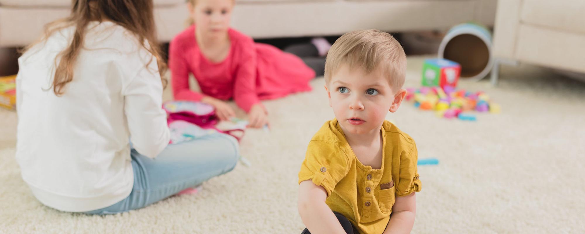 Kolme lasta leikkii leluilla matolla.