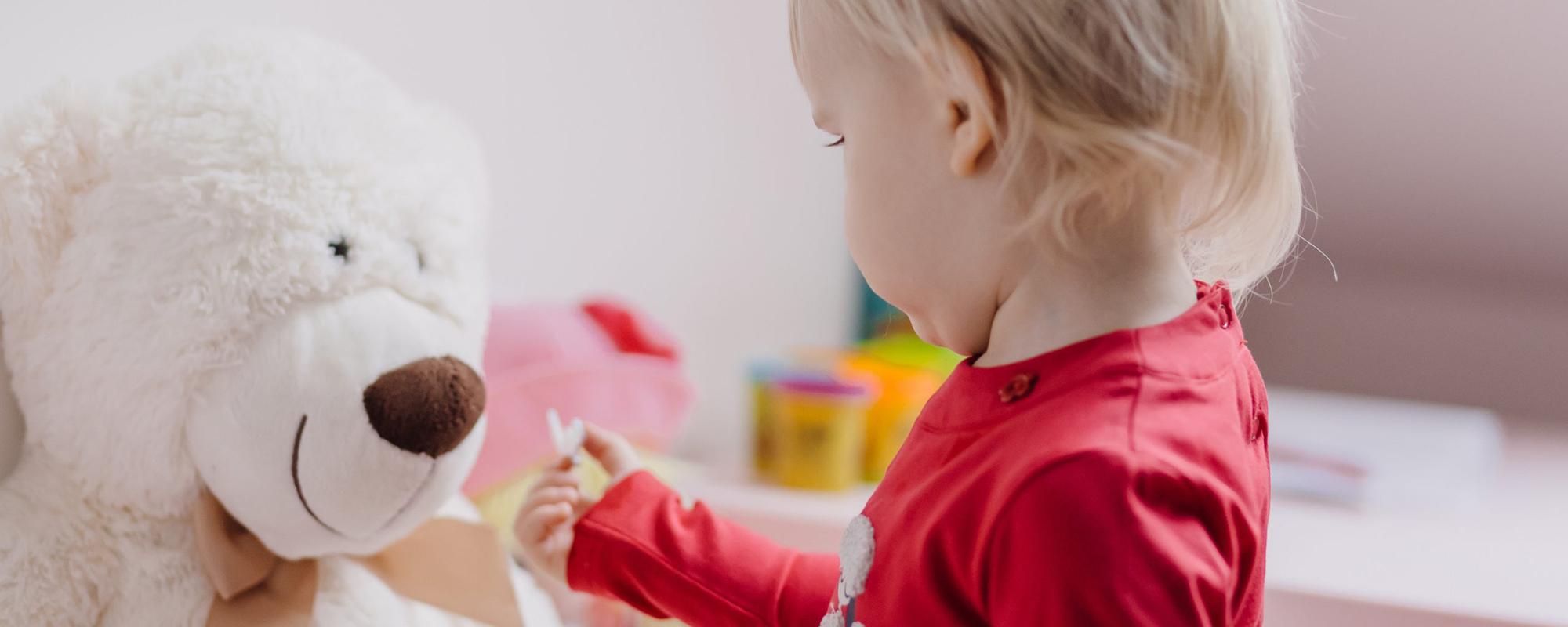Pieni lapsi näyttää nallelle lelua.
