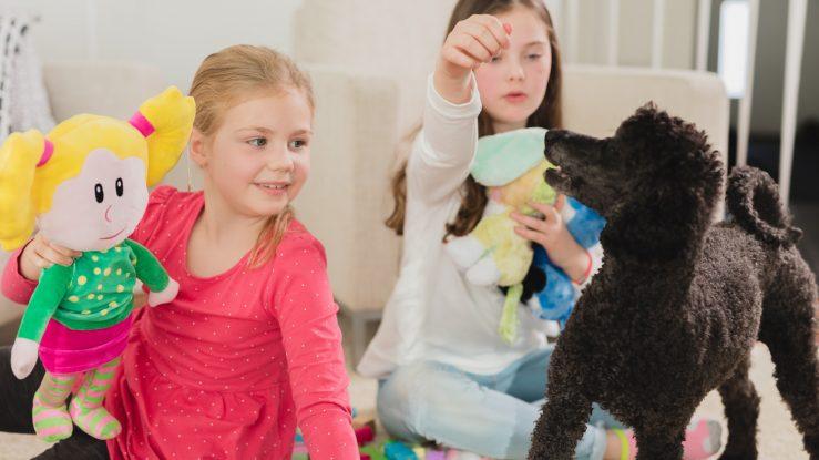 Lapset leikkimässä koiran kanssa.