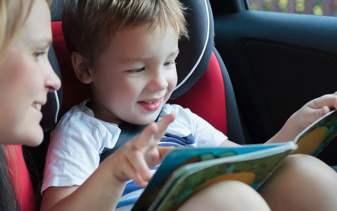 Poika lukee äidin kanssa kirjaa autossa