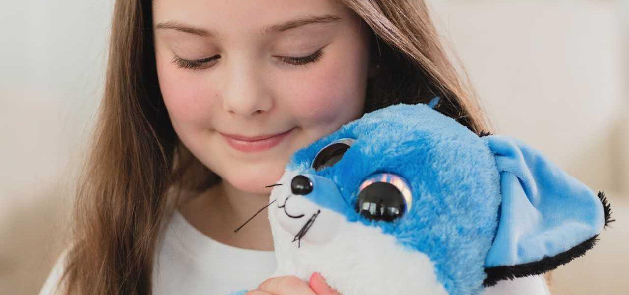Tyttö halaa sinistä pehmolelua