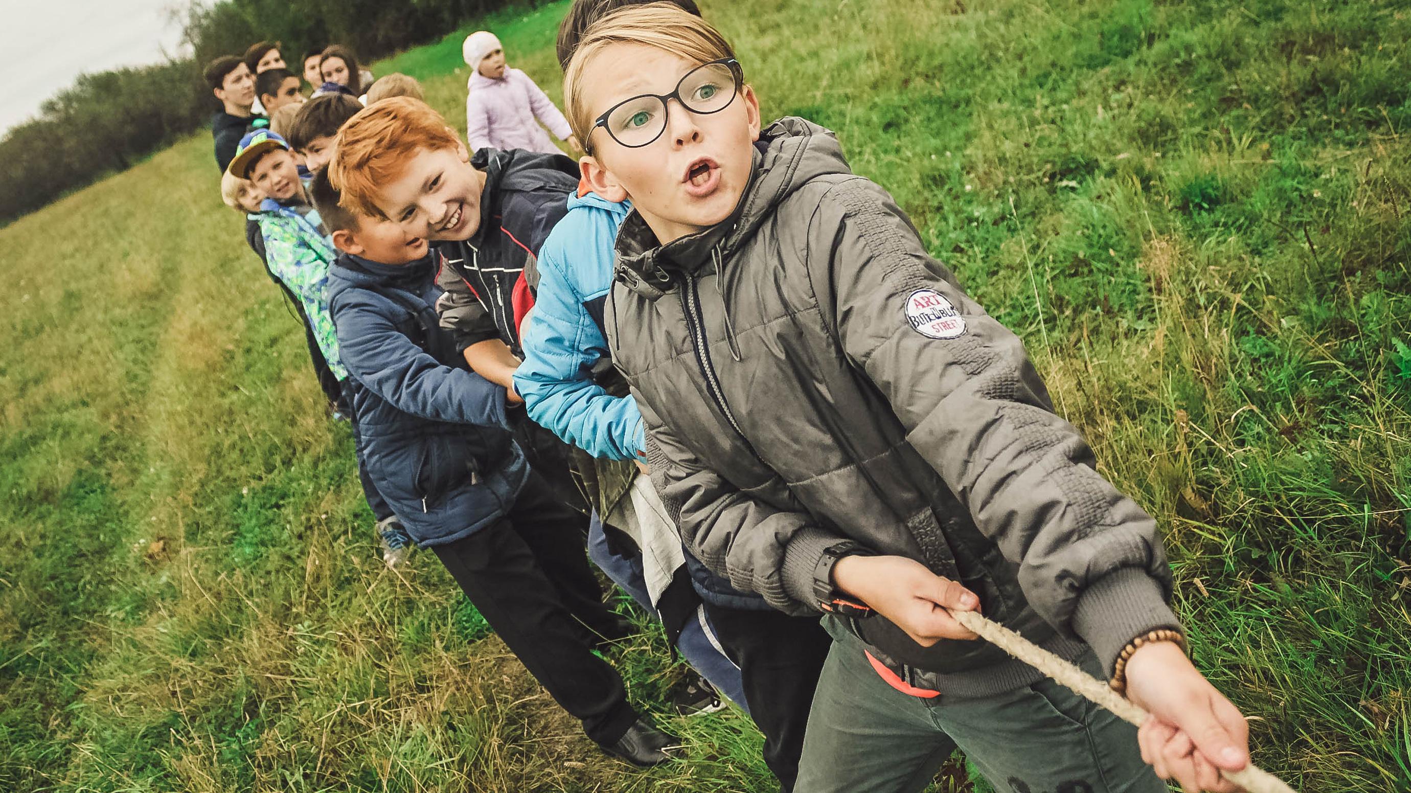 Lapset vetävät köyttä leikkiessään.