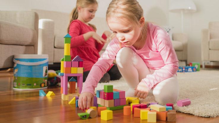 Tytöt leikkivät värikkäillä palikoilla.