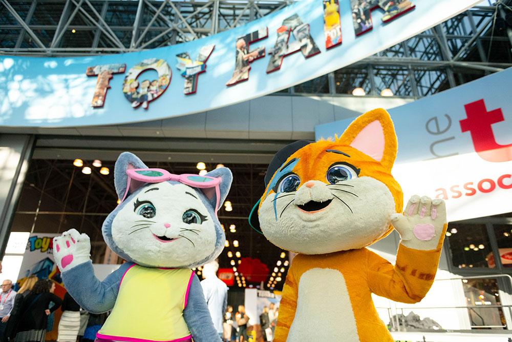 Kaksi kissapukuista maskottia New Yorkin lelumessujen kyltin alla.