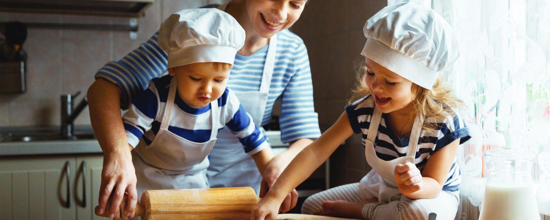 Äiti ja kaksi lasta leipovat.