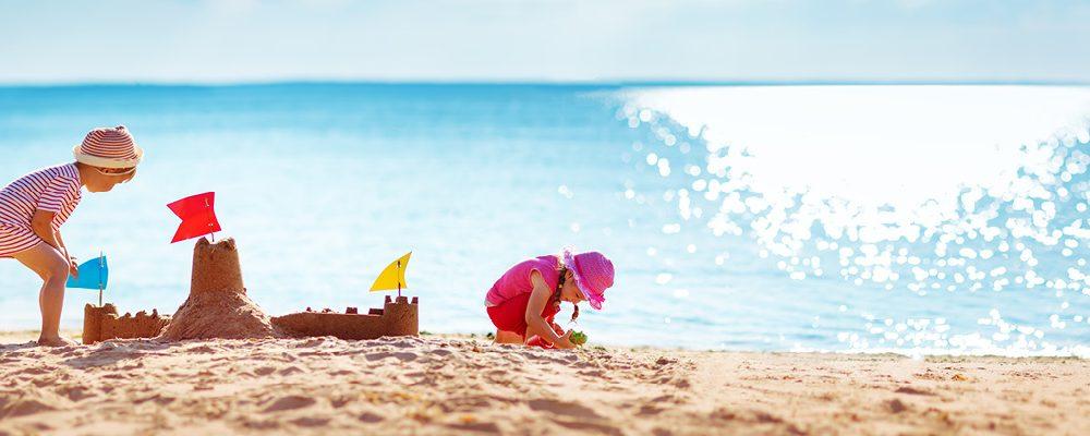 Lapset rakentavat hiekkalinnaa rannalla.